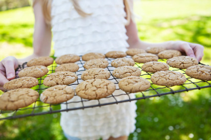 Little girl holding a wire cooling tray of freshly baked ready to eat cookies. Neighbor